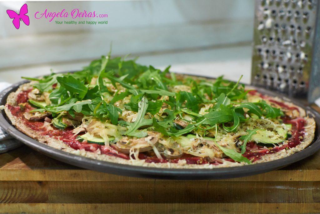 Pizza de legumes numa base de pizza e um ralador de queijo
